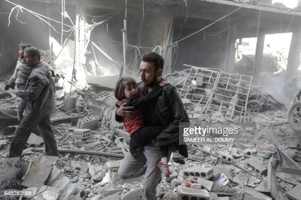 TOPSHOT Syrian men evacuate children from the rubble of destroyed buildings following reported government airstrike on the rebelheld town of Douma on...
