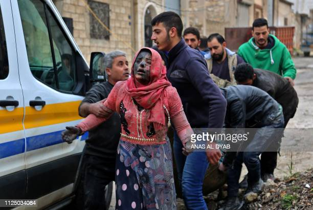 Syrian men help a wounded woman covered in dust following a strike in the town of Khan Shaykhun in the southern countryside of the rebelheld Idlib...