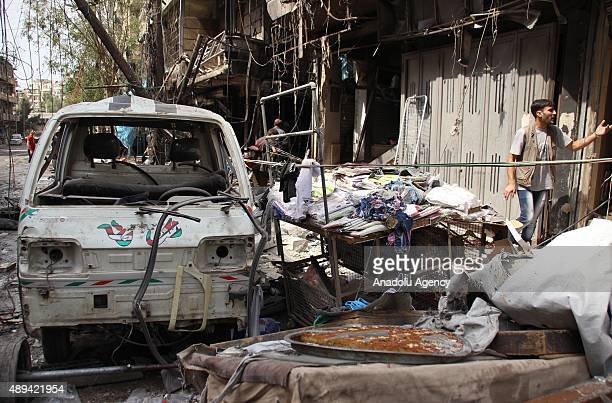 Syrian men inspect the site of bomb attacks by Assad regime forces on a market in the opposition controlled alShaar neighbourhood of of Aleppo Syria...