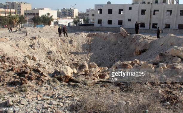 TOPSHOT Syrian men look at a crater on February 7 following a reported air strike the previous night on the northwestern city of Idlib / AFP /...