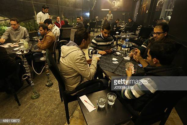 Syrian men play cards at a cafe in the Mogambo neighbourhood on the government controlled side of Aleppo on November 15 2014 Syria's government has...