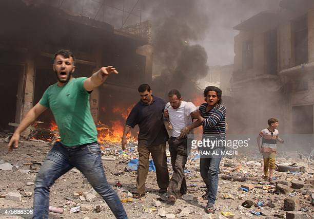 Syrian men react and help the inured following a reported barrel bomb attack by Syrian government forces that hit an open market in the northern city...