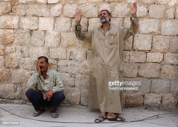 Syrian men react following a reported barrel bomb attack on the Bab alNairab neighbourhood of the northern Syrian city of Aleppo on August 25 2016 At...