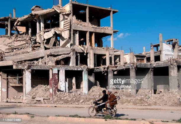 Syrian men ride a motorcycle past a destroyed building in the Islamic State group's former Syrian capital of Raqa in northern Syria, on February 19,...