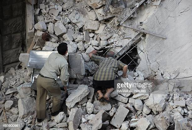 Syrian men search the rubble for survivors in a destroyed building following reported barrel bomb strikes by Syrian government forces on May 26 2014...