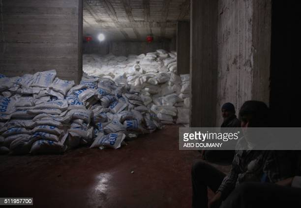 Syrian men sit near sacs at a warehouse following a Red Crescent delivery of humanitarian aid in Kafr Batna in the rebelheld Eastern Ghouta area on...