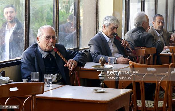 Syrian men smoke waterpipes at a cafe in the capital Damascus on February 27 as the first major ceasefire of the fiveyear war takes hold and an...