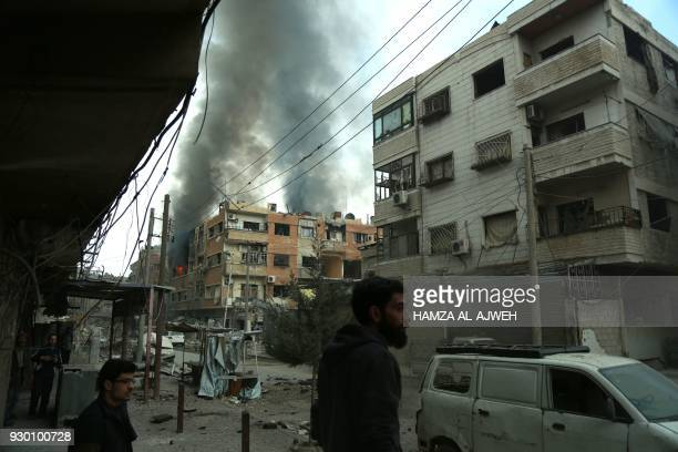 Syrian men stand as smoke billows in the background following Syrian government shelling on the town of Douma in the rebelheld enclave of Eastern...