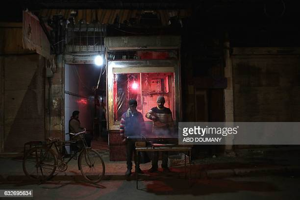 TOPSHOT Syrian men stand next to a grill outside a small restaurant in the rebelheld town of Douma on the eastern outskirts of the capital Damascus...