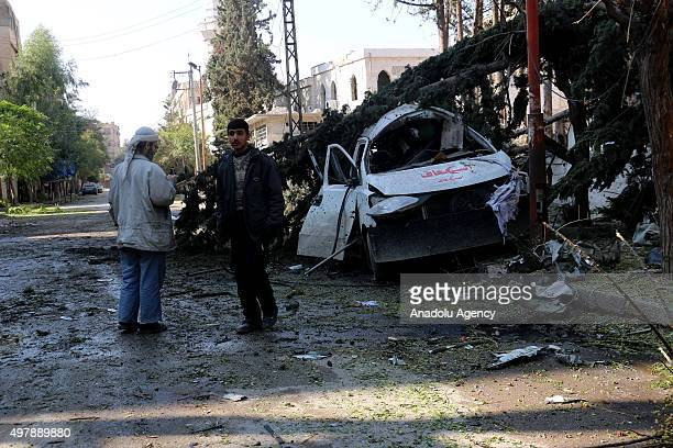 Syrian men stand next to the wreckage of a car after Assad regime forces' air attacks on an opposition controlled residential area in Douma town in...