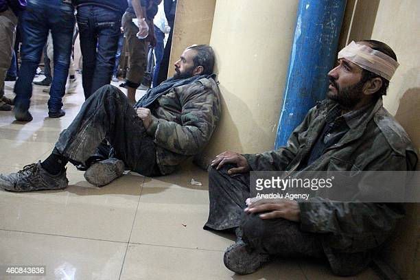 Syrian men wait for first aid as they wounded after Syrian Regime air forces' 'vacuum bomb' attack killed 6 people 3 of them children and wounded 40...