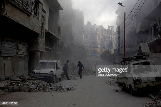 Syrian men walk on a street covered with dust following reported air strikes by forces loyal to President Bashar alAssad in the rebel held area of...