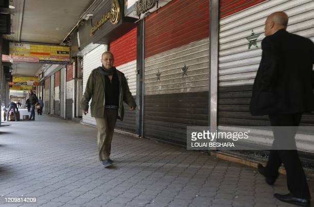 Syrian men walk past closed shops, due to the coronavirus pandemic, in the Salhiyeh neighbourhood of the capital Damascus on April 14, 2020.