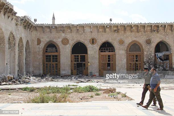 Syrian men walk through yard of Umayyad Mosque destroyed after clashes between Asad regime forces and Syrian opponents in Aleppo Syria on September...