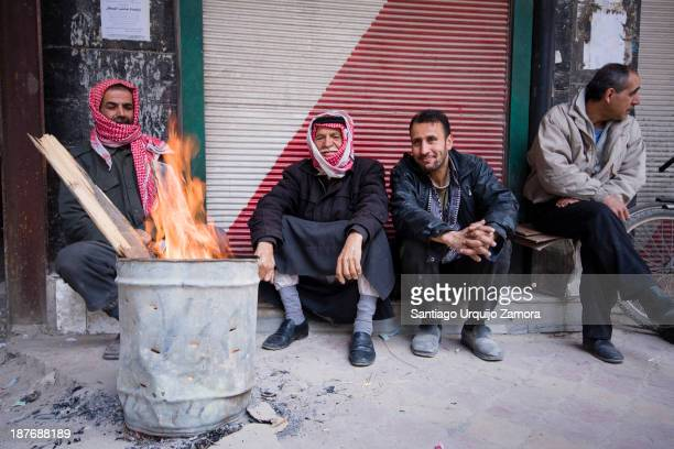 Syrian men warming up with a fire on a street of Damascus, Damascus, Damascus Governorate, Syria. Discontent against the government was strongest in...