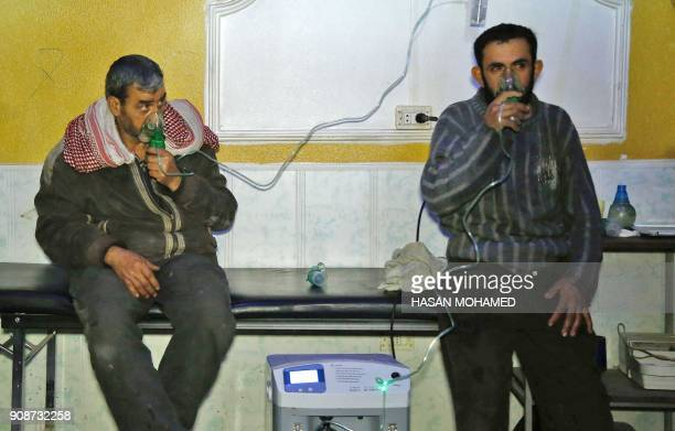 Syrian men wear oxygen masks at a makeshift hospital following a reported gas attack on the rebelheld besieged town of Douma in the eastern Ghouta...