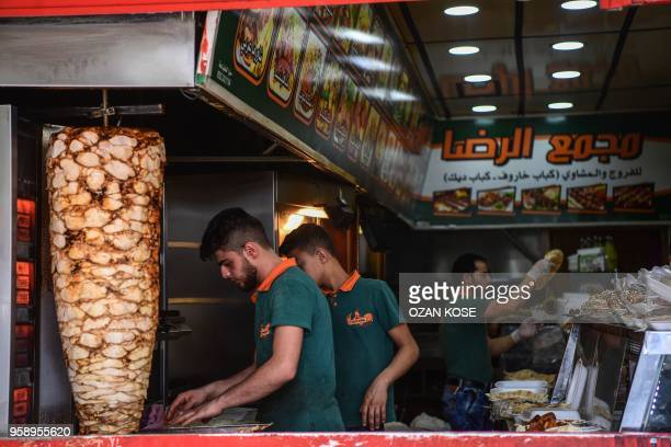 Syrian men work in a restaurant in Gaziantep in the southwest province of Turkey on May 1 2018 In the Turkish city of Gaziantep home to around half a...