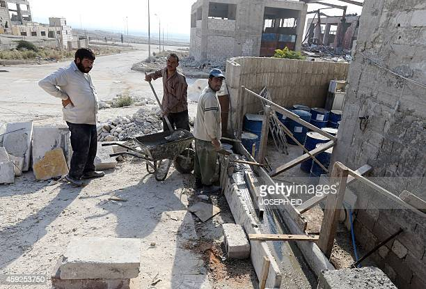 Syrian men work to rebuild a factory in Aleppo's industrial area in the government controlled side of the wartorn northern Syrian city on November 18...