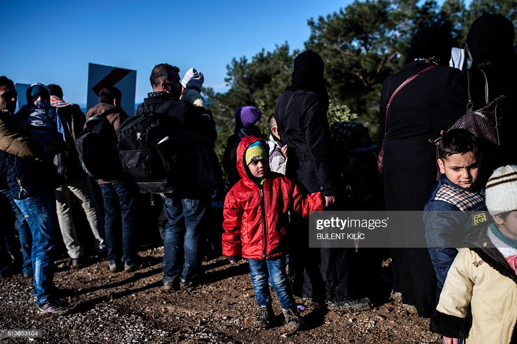 A Syrian migrant child detained by Turkish soldiers stand on a trail with other Syrian people trying to reach the Greek island of Lesbos near the village of Dikili, western Turkey, on March 5, 2016. The number of migrants crossing the Aegean Sea from Turkey to EU territory remains 'far too high', EU President Donald Tusk said after talks with Prime Minister Ahmet Davutoglu in Ankara on March 3, 2016. 'We agree the refugee flows still remain far too high and that further action is needed,' Tusk said, while praising Turkey for its growing cooperation including stepped-up coastguard patrols and a tightening of its visa regime. / AFP / BULENT