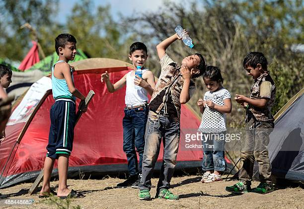 Syrian migrant children refreshes with a bottle of water as they rest during their walk towards the Greece border on a road near Edirne September 16...
