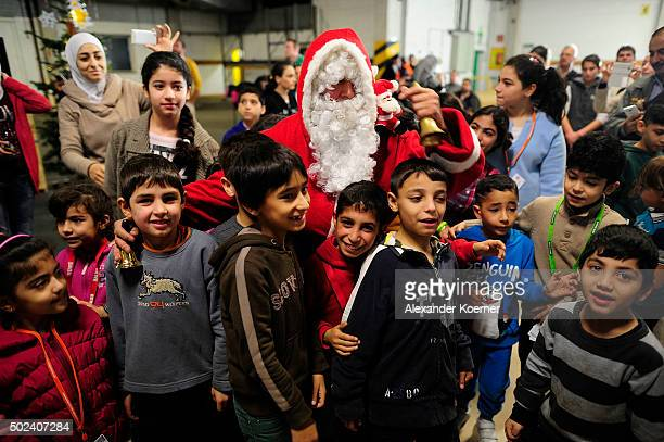 Syrian migrant dressed as Santa Claus greets children at a shelter for migrants and refugees on December 24 2015 in Sarstedt Germany Thousands of...