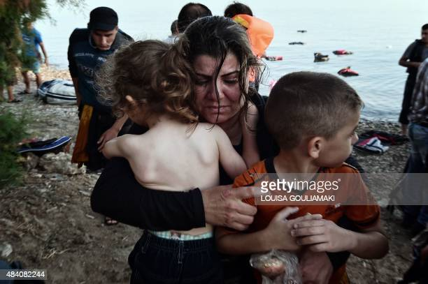 A Syrian migrant holds her children as they arrive on an overcrowded dinghy on a beach near the port on the Greek island of Kos on August 15 2015 A...
