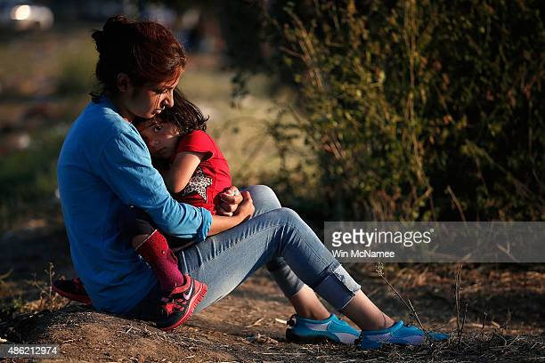 Syrian migrant holds her daughter as they wait to be processed across a border crossing into Macedonia for migrants September 2 2015 in Idomeni...