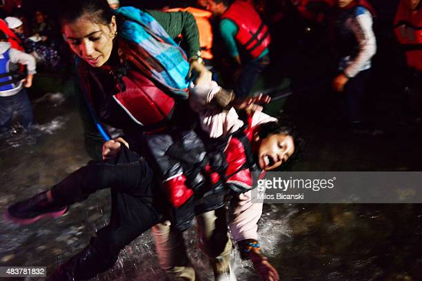 Syrian migrant mother carries her child as they arrive at a beach on the Greek island of Kos after crossing a part of the Aegean sea from Turkey to...