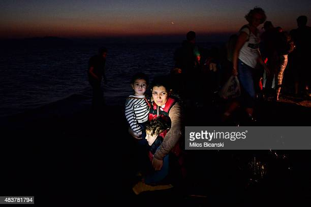 Syrian migrant mother holds her two children as they arrive at a beach on the Greek island of Kos after crossing a part of the Aegean sea from Turkey...