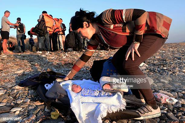 Syrian migrant mother with a 10 month old baby arrives at a beach on the Greek island of Kos after crossing a part of the Aegean sea from Turkey to...