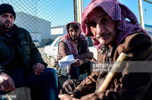 TOPSHOT Syrian migrants and refugees wait in front of the Turkish Oncupinar crossing gate near the town of Kilis to return to Syria on February 9...