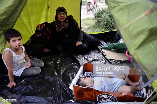 Syrian migrants are seen at a makeshift camp in the centre of town on August 12 2015 in Kos Greece Greek police used fire extinguishers and batons to...
