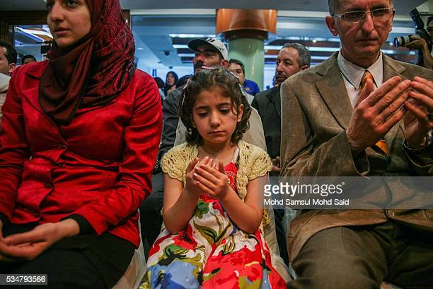 Syrian migrants from the Bekka Valley refugee camp in Lebanon pray upon arrival at the Royal Malaysian Air Force Base on May 28 2016 in Subang Jaya...