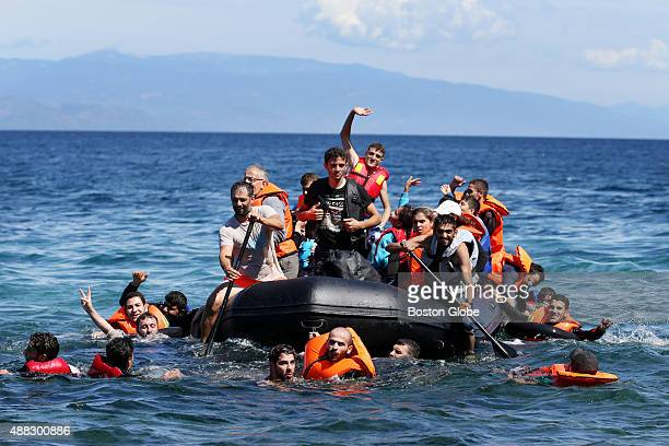 Syrian migrants many of them refugees push and pull their boat through the Mediterranean Sea as they approach the shore near Skala Sykamnia on the...