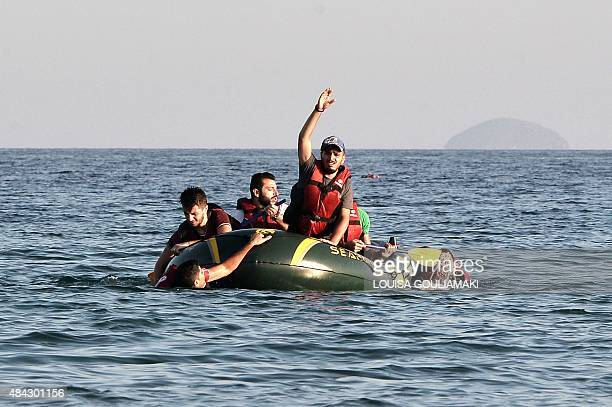 Syrian migrants try to make it to shore in their halfsunk dinghy as they arrive on the Greek island of Kos on August 17 2015 Their small engine broke...