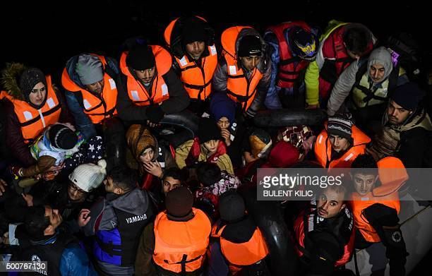 TOPSHOT Syrian migrants wait aboard an inflatable dinghy after being rescued while attempting to reach the Greek Island Chios on the Agean Sea near...