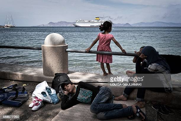 Syrian migrants watch the arrival of the Eleftherios Venizelos ferry from their makeshift encampment on the coast of the Greek island of Kos island...