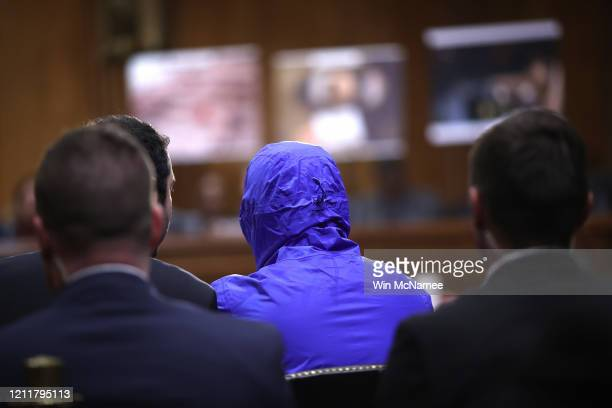 Syrian military defector using the pseudonym Caesar wears a blue hood to conceal his identity while testifying before the Senate Foreign Relations...