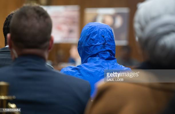 Syrian military defector using the pseudonym Caesar, while also wearing a hood to protect his identity, testifies about the war in Syria during a...