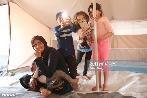 Syrian mother breastfeeds her son as her daughter takes a photo next to other children in their tent at the Moria refugee camp on May 20 2018 in...