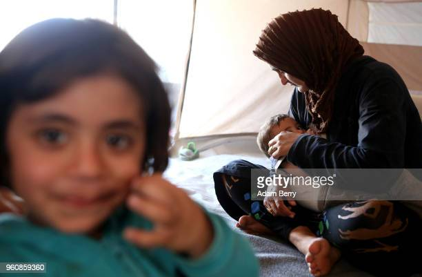 Syrian mother breastfeeds her son in their tent at the Moria refugee camp on May 20 2018 in Mytilene Greece Despite being built to hold only 2500...