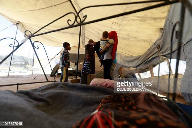 A Syrian mother displaced from her home in Deir Ezzor dresses her child with clothes received as part of humanitarian aid provided by the United...