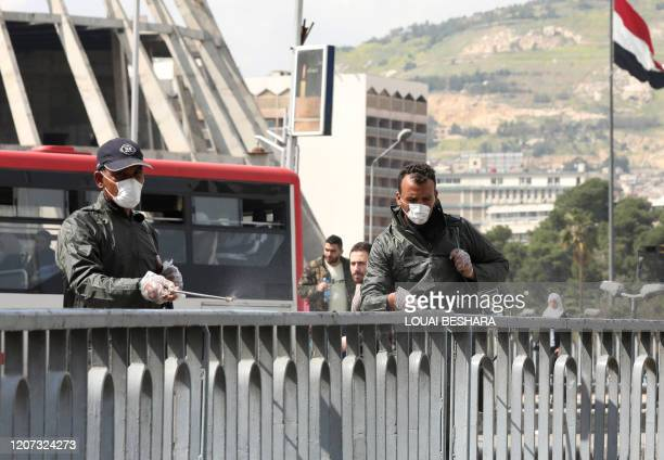 Syrian municipal workers spray disinfectant against the COVID-19 coronavirus in Damascus on March 16, 2020.