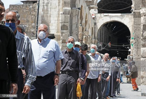 Syrian Muslim men wearing face masks, queue to enter the Umayyad Mosque in Damascus to attend the Friday prayer on May 15 following the authorities'...