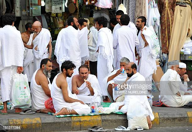 Syrian Muslim pilgrims eat their food on the pavement of the Haram street near the Grand Mosque on the eve of the start of the annual Hajj pilgrimage...