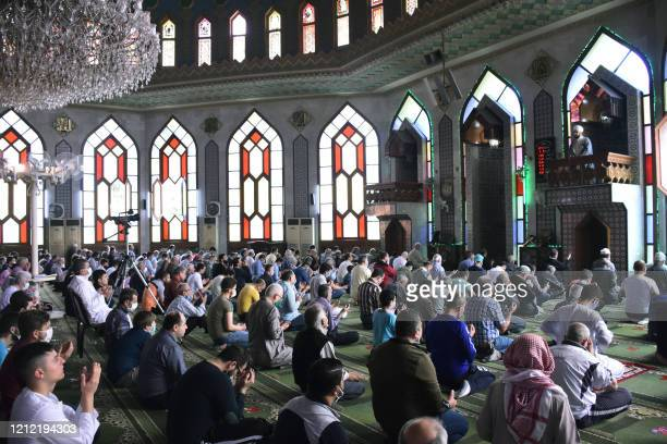 Syrian Muslim worshippers, some wearing masks against the coronavirus Covid-19, pray at a mosque during the hoy month of Ramadan in Aleppo in...