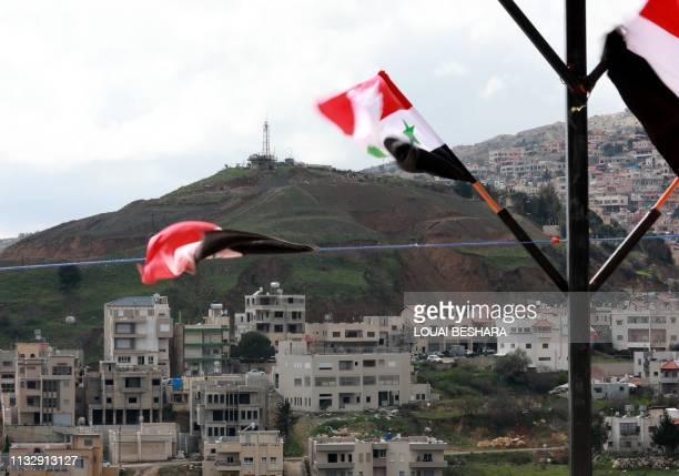Syrian national flags are flown in the Syrian town Ain alTineh across from the Majdal Shams in the Israeli annexed Golan Heights on March 26 2019 US...