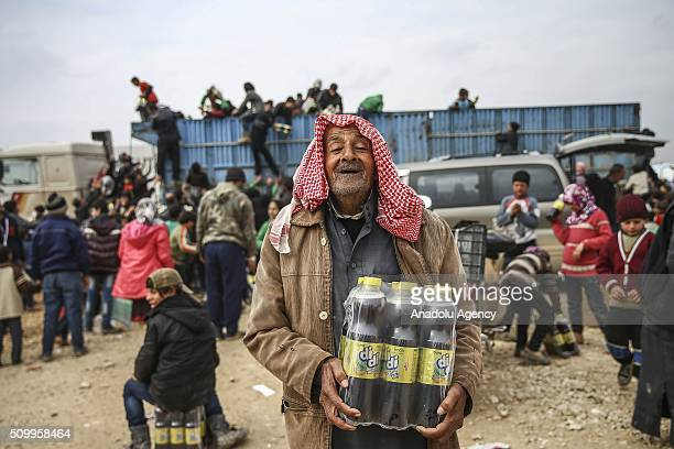 Syrian old man who fled bombing in Aleppo gestures and carry beverages distributed by Turkish Humanitarian organization at a tent city close to the...