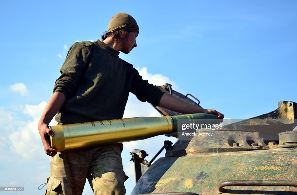 A Syrian opponent places a weapon before attacking Daesh terrorist organization's positions with the howitzers in the Herbel village of the Mari district in Aleppo, Syria on November 1, 2015.