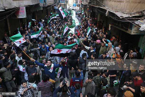 Syrian opponents chant slogans and hold Syrian flags during a protest against Assad Regime after Friday prayers at the alSukkari neighborhood of...